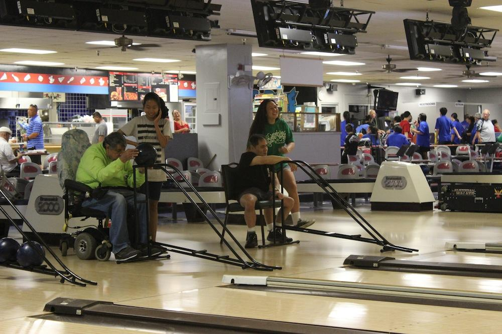 Club Med volunteers help handicapped bowlers once a month at Fort Shafter bowling alley. The program was begun 40 years ago by an Academy graduate.