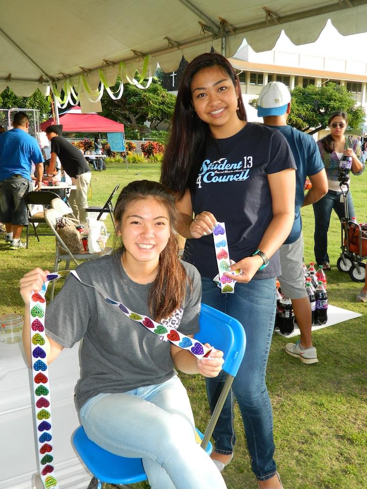 Student council members, Pamela Nishida and Caroline Kikkawa, passed out stickers to participants at their game booth, Lancer Luck, at the Year of Faith celebration.