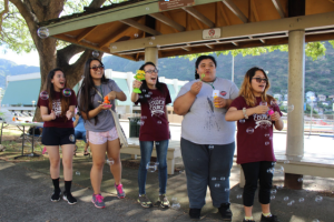 Seniors Dana Fuerte, Maya Mathur, Risa Hiyashida, Asenita Tuiafitu and Angelique Mara show their enthusiasm in greeting students at Palolo Park.