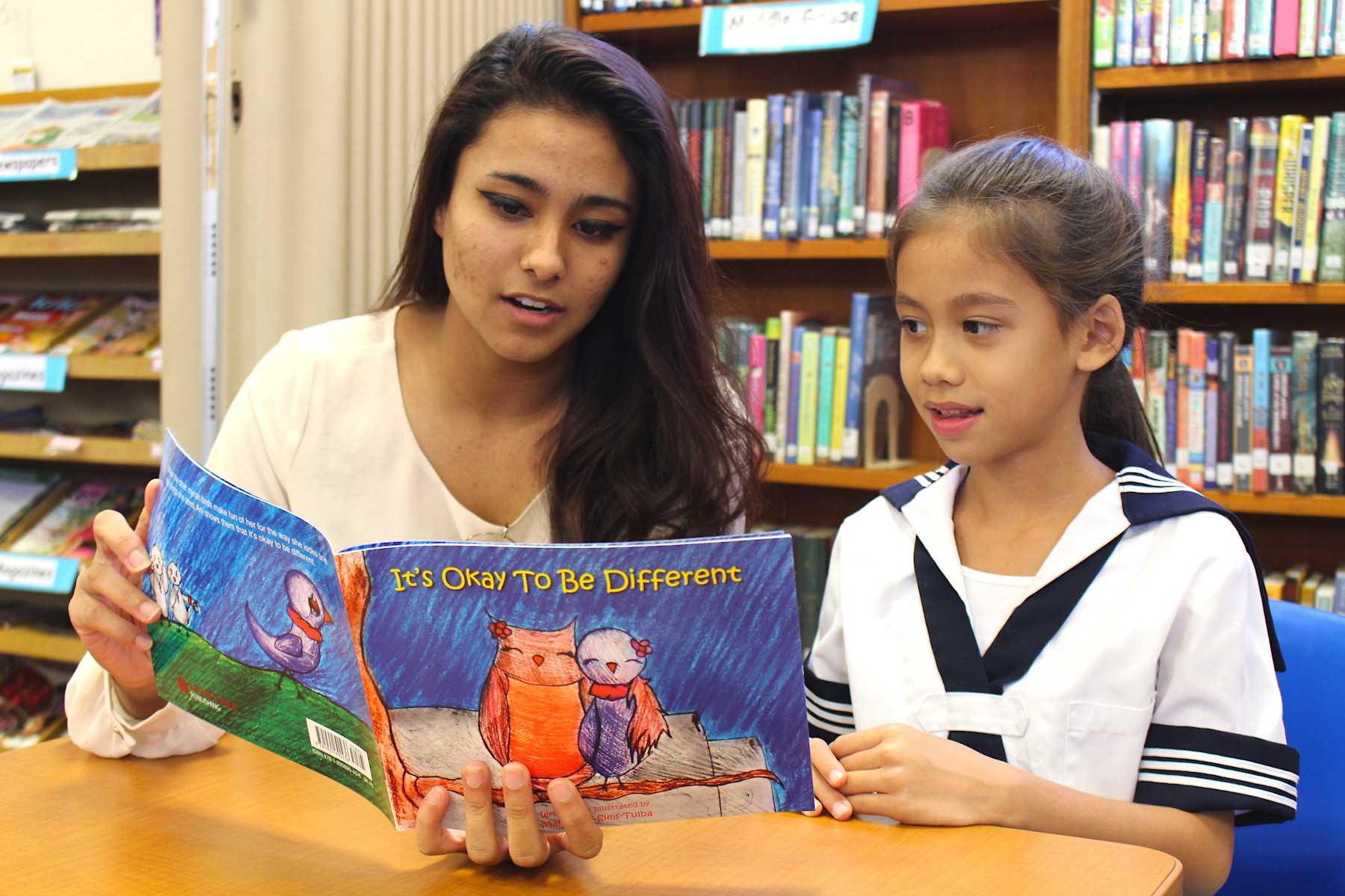 Junior Mahealani Sims-Tulba reads her book to second grader Leilani Freitas.
