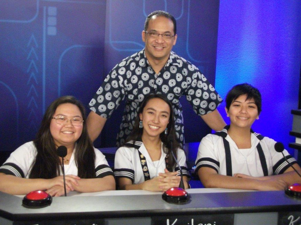 "A great filming session is never complete without a photo. Seniors Janelle Lauronal, Kailanianna Ablog and junior Katherine Christian are all smiles with ""It's Academic Hawaii"" host and Hawaii News Now reporter Billy V.  Photo courtesy of Lurline Choy."