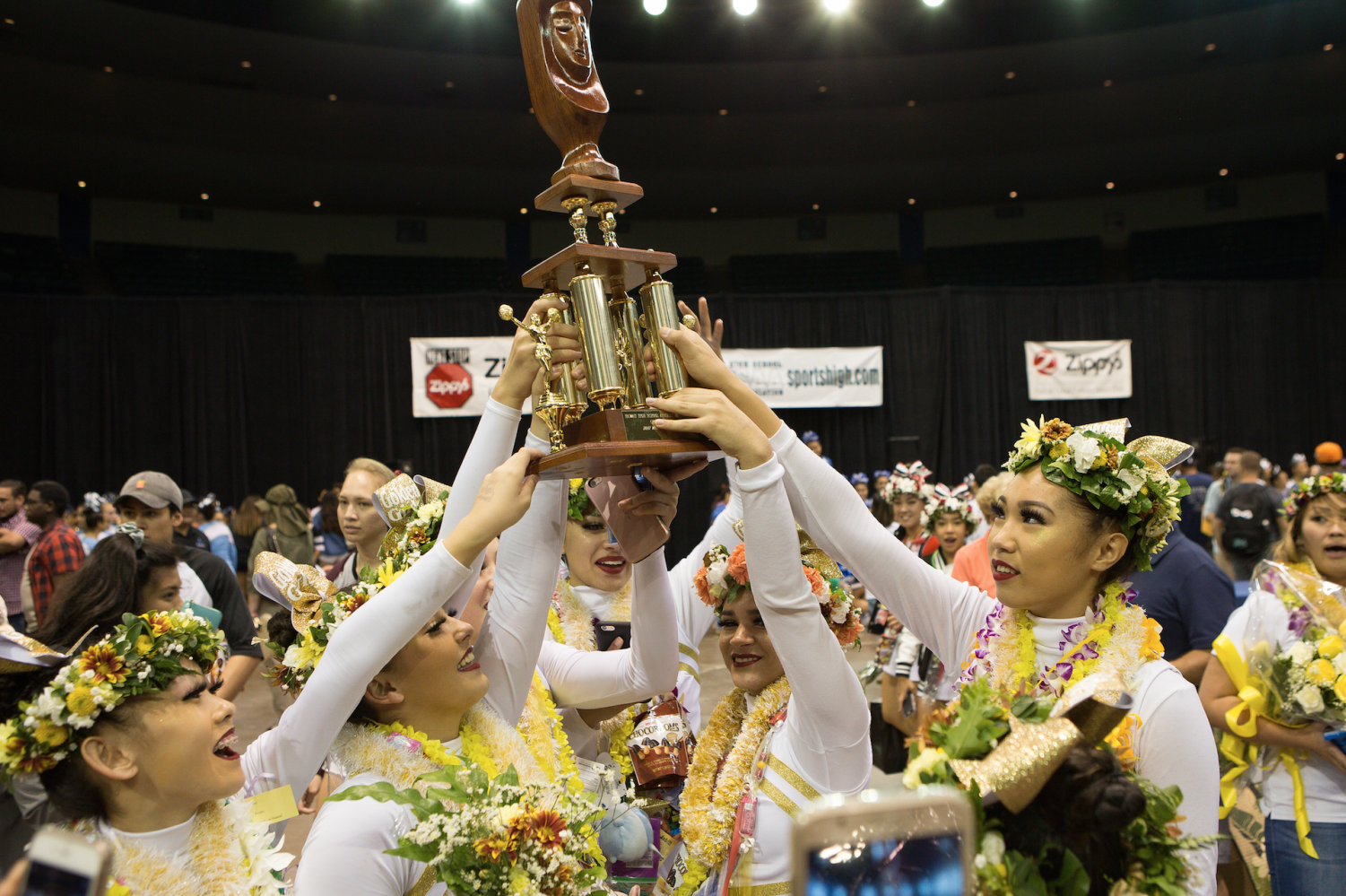 The Academy's varsity cheerleading team, also known as the Golden Girls, hold their trophy after winning first in the medium division. Photo courtesy of 808 Hot Shots.
