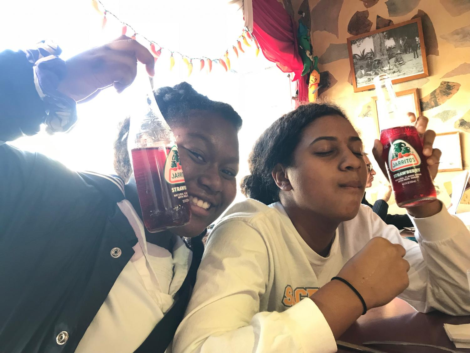 Sophomores Destiny Carter and EjaLee Chavis  share a strawberry soda from Mexican restaurant Aztec. Photo by Noe Nekotani.