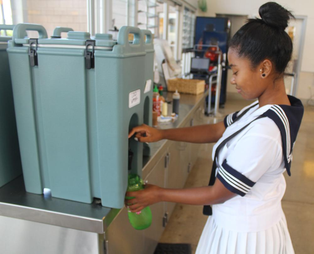 Sophomore Rhythm Ogawa-Goodman uses the student center water containers to refill her bottle.  The cafeteria has stopped supplying students with cups and hopes to reduce paper waste.