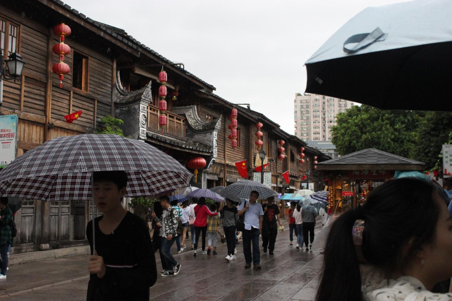 Customers brave the rainy weather for the wares sold at Three Lanes and Seven Alleys.
