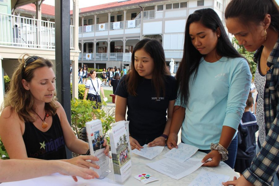 Sophomores Amanda Giang and Kaila Kawamura-Jeremiah, along with Junior Tia Sagapolu, drops by one of the event's informational booths to learn more facts about human trafficking. All photos by Noe Nekotani.