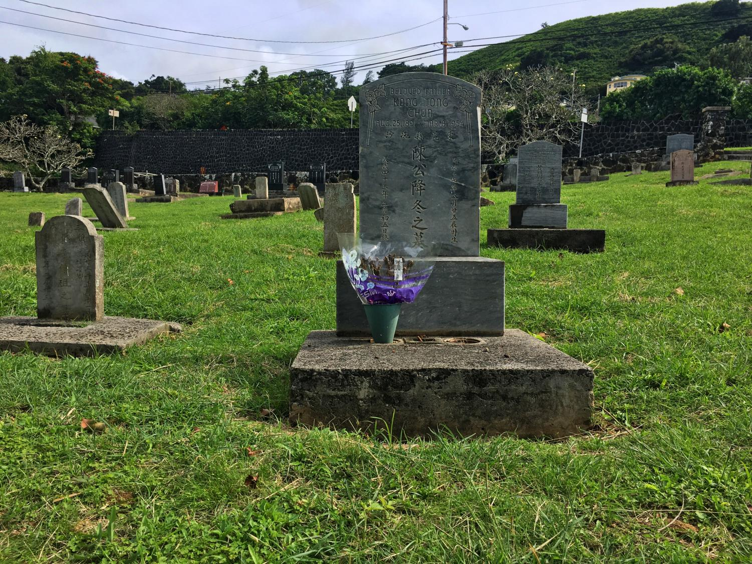 """A traditional gravestone found at a Manoa cemetery. Before taking the """"Dying and Rising"""" theology course, many Sacred Hearts Academy students believed that cremation and burials were the only options for the dead. This class prompts students to research other death rituals and to take steps toward planning their funeral and writing their eulogy. Photo by Taylor McKenzie."""