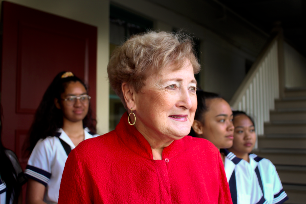 Head of School Betty White starts her day with morning flag, where she stands surrounded by Sacred Hearts Academy students. White, a leader in Catholic education, retires in July after more than 60 years at the Academy as a teacher and then administrator. Photo by Kirsten Aoyagi.