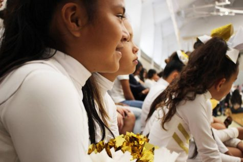 The intermediate cheer team, dressed in gold and white, listen to opening remarks at this year's Founder's Day Assembly. The Academy celebrates 110 years. During their performance, the cheer team shares the same routine from a recent Interscholastic League of Honolulu (ILH) competition. At this competition a few weeks ago, the intermediate team placed first. All photos by Rheamae Ibarra.